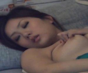 Japanese babe rubs pussy
